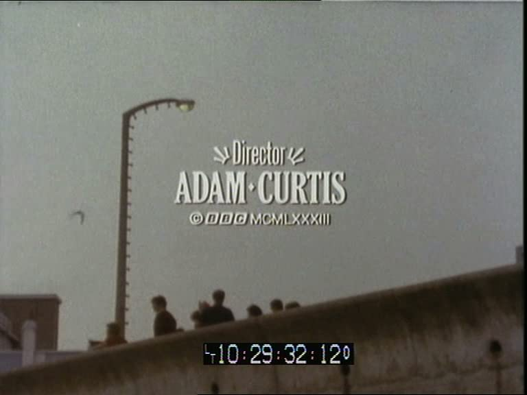 A still from a grainy video, showing people at a seafront, with text reading 'Director: Adam Curtis'