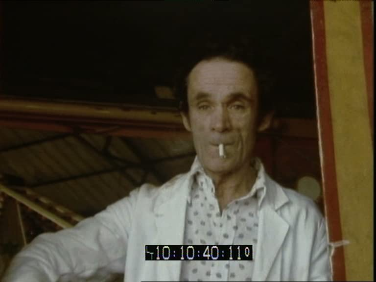 A video still showing a man in a white coat, with a white cigarette drooping from his mouth.