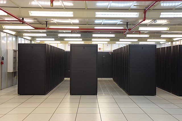 A photo of large black computer cabinets in a large white room.