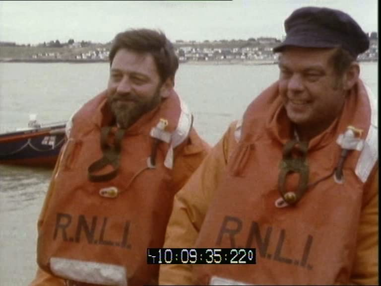 A video still of two smiling middle-aged men wearing orange life vests with R.N.L.I written on the front.