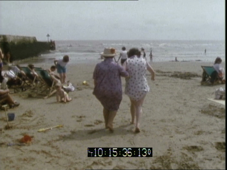 A video still of a beach with two women, arm-in-arm, walking away from the camera towards the sea.