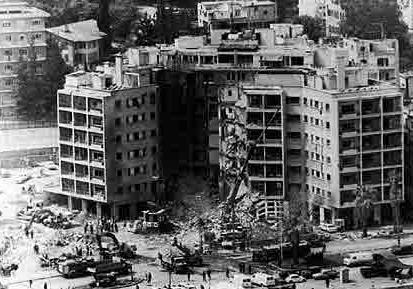A black and white photo showing a bombed multi-storey building.