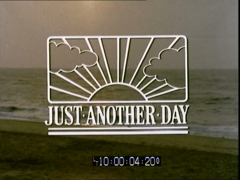 A frame from a video of a beach and the sea with a title over the top reading 'Just Another Day'.