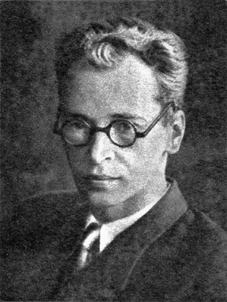A black and white portrait photo of a young man wearing a suit and tie and round black-framed glasses.