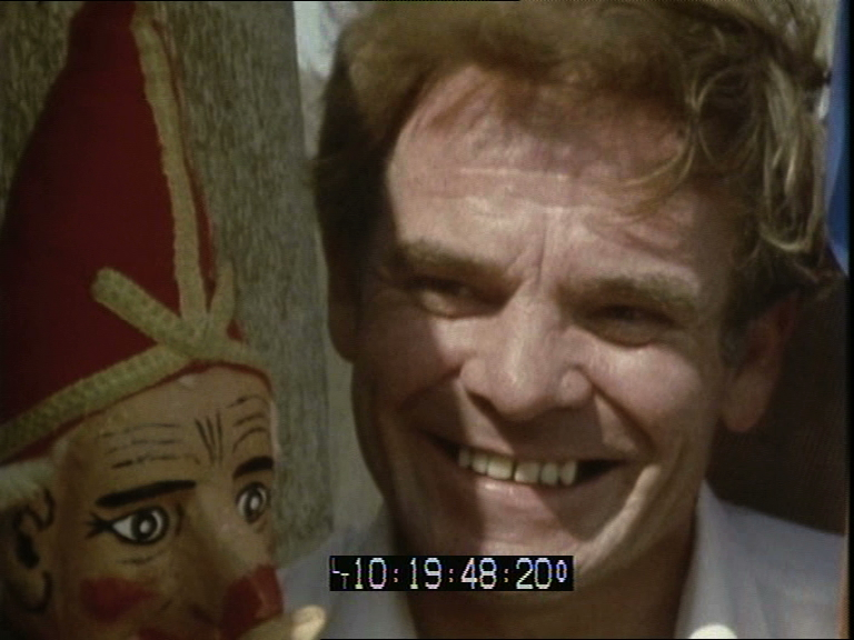 A video still showing a smiling middle-aged man and the head of a Punch puppet.