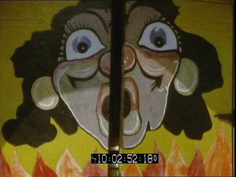 A video still showing the doors of a ghost train ride, with a shocked or surprised face painted on them.