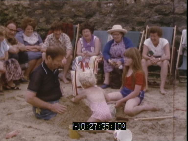 A video still showing men and women in a line of deckchairs watching a toddler and a young girl burying a man's legs in sand.