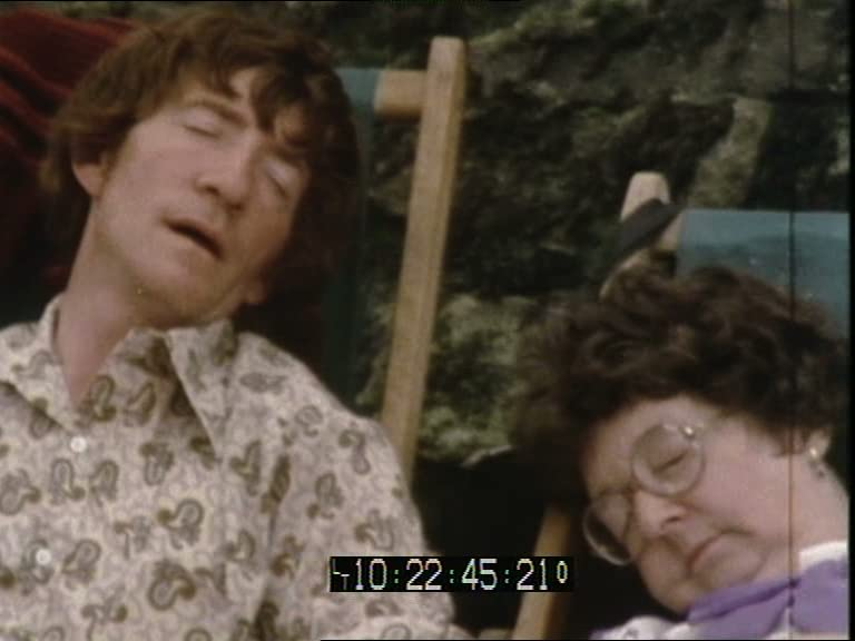 A video still showing a man and a woman asleep in their deckchairs.