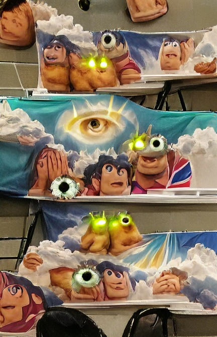 This looks like three shelves, each holding several odd pale brown shapes that sometimes have eyes and mouths, looking like melted children's toys. Potatoes? Aliens? Some have bright green eyes and maybe antennas. Some have black and white googly eyes. Some have a single, large human iris and pupil. Behind them are what look like bits of cloth painted with blue sky and clouds, one with a hovering god-like eye radiating yellow light.